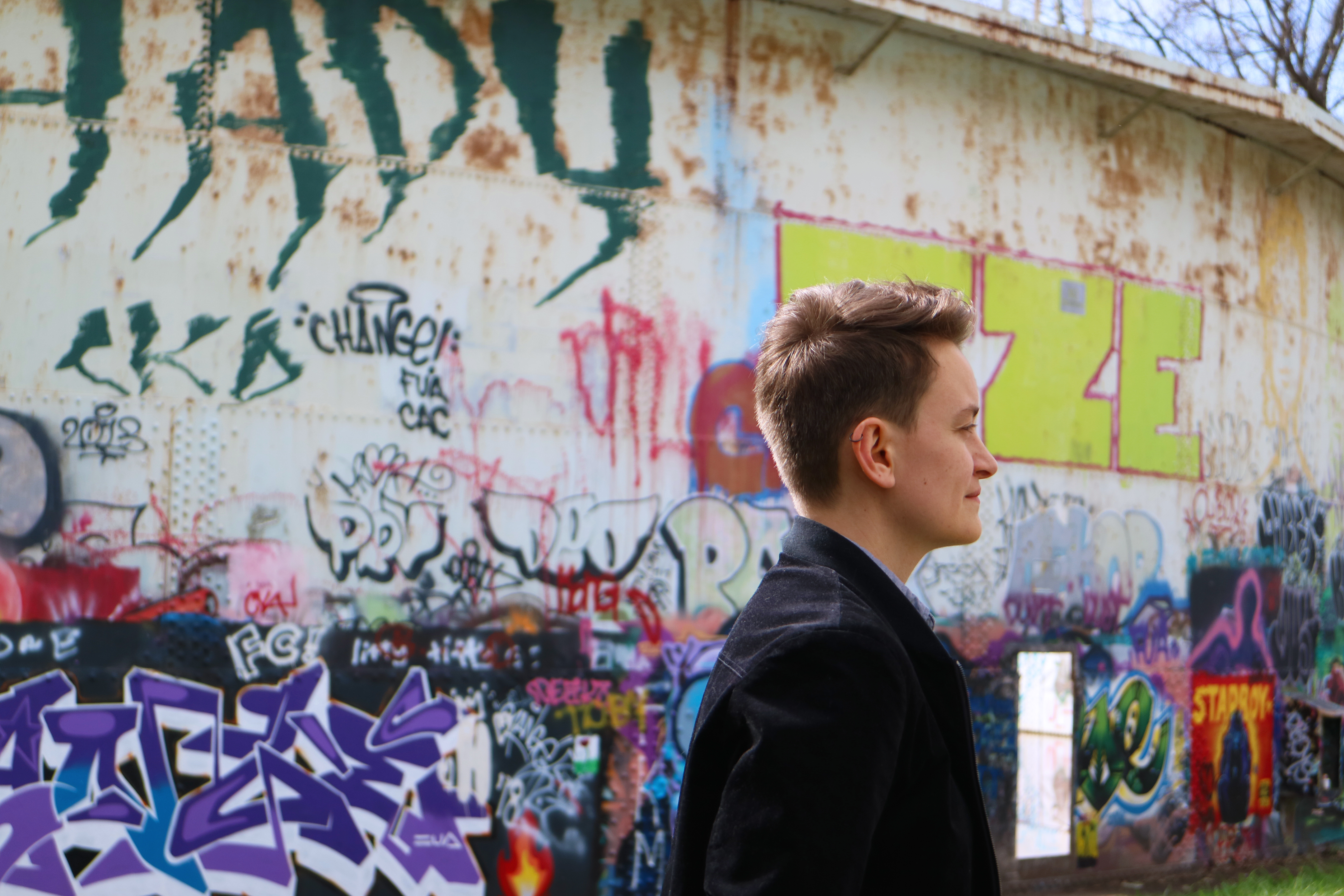 Photo of Julia Tulke standing in profile in front of a wall of graffiti